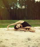 Beautiful girl is engaged in yoga in the forest on the sand Royalty Free Stock Photos