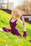 Girl doing yoga on green grass on a sunny day royalty free stock images