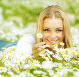 Beautiful girl enjoying daisy field. Beautiful woman enjoying daisy field, nice female lying down in the meadow of flowers, pretty girl relaxing outdoor, having stock image