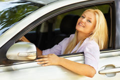 Beautiful girl enjoying her new car. Attractive blonde young woman at the wheel in her new car Stock Image