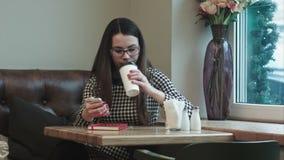 Beautiful girl enjoying an hot coffee in cafe with window stock video footage