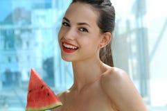 Beautiful girl enjoying life with watermelon. Beautiful girl enjoying life and eating a triangular slice of watermelon outdoors Royalty Free Stock Photo