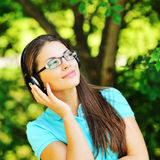 Beautiful girl enjoying music in a summer green park Royalty Free Stock Images