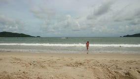 Beautiful girl enjoying summer beach holidays comes into the sea. Travel vacation of happy woman in bikini.  stock video footage