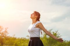 Beautiful girl enjoying the sun with her arms outstretched in the field against the sky royalty free stock photos
