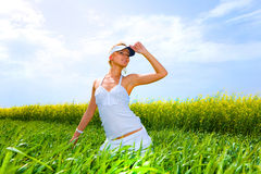 Beautiful girl enjoying the sunny weather. In the middle of a field. In a white dress Stock Photos