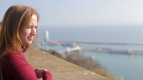 Beautiful girl enjoying view of sunny Barcelona. Beautiful girl in red enjoying view of sunny Barcelona from the top of moutain stock footage