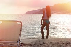 Beautiful girl enjoys the sunset on the beach. Rest and relaxation Stock Images