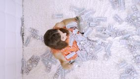 A beautiful girl enjoys tremendous wealth. female sorting out a lot of banknotes on a white bed, throws up money, slow. Motion, top view stock video footage