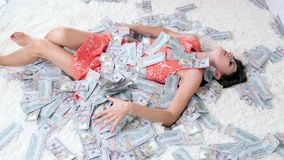Beautiful girl enjoys tremendous wealth. female throws up a lot of banknotes on a white bed, throws money, top view.  stock footage