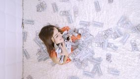 Beautiful girl enjoys tremendous wealth. female throws up a lot of banknotes on a white bed, throws money, top view.  stock video footage