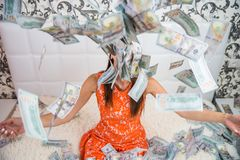 Beautiful girl enjoys tremendous wealth. female throws up a lot of banknotes on a white bed, throws money, top view