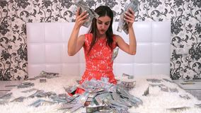 Beautiful girl enjoys tremendous wealth. female throws up a lot of banknotes on a white bed, throws money, top view.  stock video