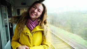 Beautiful girl enjoys  trip and with broad smile showing gestures, stands in  train near  window in  afternoon fall. Portrait of cheerful female in train near stock video