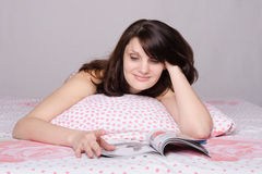 Beautiful girl with enthusiasm reads magazine in bed Royalty Free Stock Photo