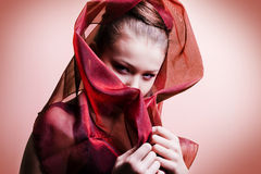 Beautiful girl enveloped  in red headscarf Royalty Free Stock Image