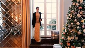 A beautiful girl in an evening dress and a black mink coat comes into the room decorated with a Christmas tree. stock footage