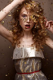 Beautiful girl in an evening dress and gold curls. Model in New Year`s image with glitter and tinsel. Stock Photo