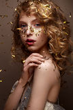 Beautiful girl in an evening dress and gold curls. Model in New Year`s image with glitter and tinsel. Stock Images