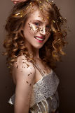 Beautiful girl in an evening dress and gold curls. Model in New Year`s image with glitter and tinsel. Royalty Free Stock Images