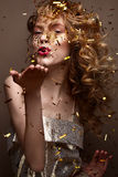 Beautiful girl in an evening dress and gold curls. Model in New Year`s image with glitter and tinsel. Royalty Free Stock Photos