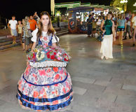 Beautiful girl in evening dress. Selling flowers on the evening promenade of Yalta Royalty Free Stock Photo
