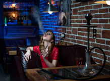 Beautiful girl in evening dress smokes a hookah in the interior of the bar. A beautiful girl in a red evening dress smokes a hookah in the interior of a loft Stock Photo