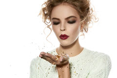 Beautiful girl with evening makeup blow gold sequins Stock Image