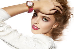 Beautiful girl with evening makeup red lips and watch. Portrait of beautiful young girl with a bright evening make-up perfect skin and blue eyes, red lips, nice Royalty Free Stock Photos
