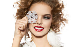 Beautiful girl with evening makeup smile take cristal snowflake. Beautiful young girl with a bright evening make-up of shiny red lipstick long fluffy eyelashes Stock Images