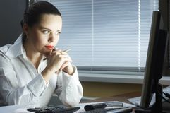 Beautiful girl in the evening sits at office Royalty Free Stock Image