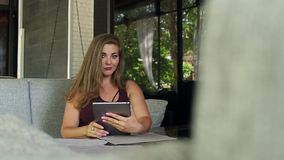 A beautiful girl with excess weight sits in a restaurant with a tablet. The fat girl is resting in a street cafe with a tablet in her hands stock footage