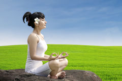 Beautiful girl exercise yoga on green field Royalty Free Stock Photo