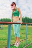 Beautiful girl exercises on the horizontal bar on the pla Stock Image