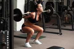 Beautiful girl exercising squatting with barbell Royalty Free Stock Photos