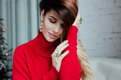 Beautiful girl eyes closed listens and smiles. Beautiful girl in a red sweater and rings eyes closed basking, she listens, caresses, rejoices, smiles in white Royalty Free Stock Photo
