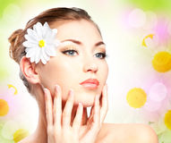 Beautiful girl face. Spa (spring) beautiful woman with camomile touching her face Stock Photography