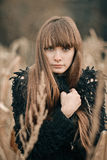 Beautiful girl face. Closeup portrait in brown, beige colors of pretty serious girl with long dark hair. Pretty serious girl hug h. Shot in war, colors of Royalty Free Stock Photo