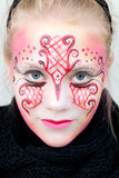 Beautiful girl with face paint. Young woman with pink, red and black face paint with a very intense gaze Stock Image