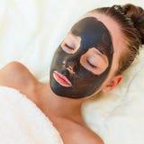 Girl with facial black clay mask. stock photos