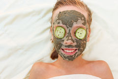Beautiful girl with facial clay, cucumber mask. Royalty Free Stock Images