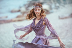A beautiful girl in a fairy light dress on a coast. A portrait of a beautiful girl in a fairy light dress on a coast Royalty Free Stock Photos