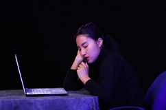 Beautiful girl faling asleep over her laptop on dark background.  Royalty Free Stock Photography