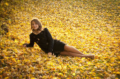 Beautiful girl on fallen yellow leaves Royalty Free Stock Photography