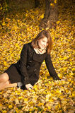 Beautiful girl on fallen yellow leaves Royalty Free Stock Images