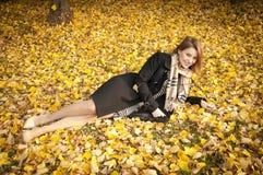 Beautiful girl on fallen yellow leaves royalty free stock photo