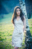 Beautiful girl in fashion dress stand by  birch Royalty Free Stock Image