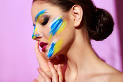 Beautiful girl fashion model with paint on her face Stock Photo