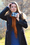 Beautiful girl in fashion pose with old camera in hand Stock Image