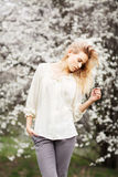 Beautiful girl fashion style in blossom garden on a spring day. Beautiful young girl in blossom garden on a spring day stock image